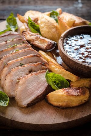 bbq sauce: Pork fillets, baked potatoes and homemade bbq sauce on wooden background,selective focus