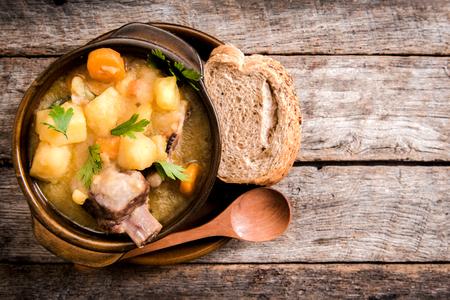 Sopa de guiso casero con verduras y costillas de carne en el cuenco rústico, enfoque selectivo y espacio en blanco