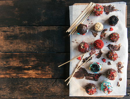 Sweet and homemade chocolate cake pops on wooden background,blank space
