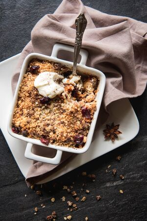apple crumble: Apple crumble cake with dried fruit on wooden background