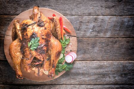 thanksgiving menu: Rosted turkey with vegetables on wooden background with blank space