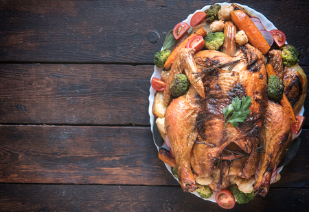 traditional christmas dinner: Split toasted turkey on the table with vegetables,from above and blank space Stock Photo