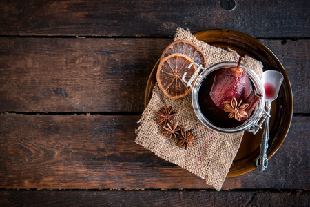 dessert plate: Served cooked pears in wine on wooden background with blank space Stock Photo