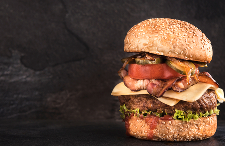 no way out: Juicy beef burger in the sesame bun and bacon with onion on dark background,blank space