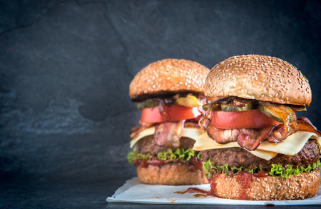 Two beef burgers with bacon,grilled onion and pickles,selective focus and blank space