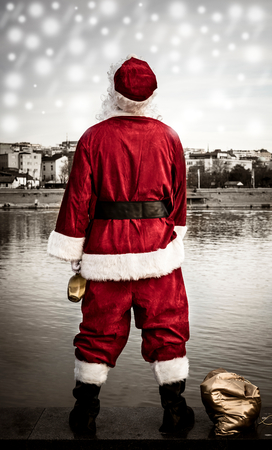Bad Santa holding bottle of brandy and standing on river docks watching the city Stock Photo