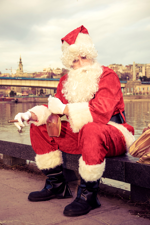 claus: Sad Santa Claus with ciggar and bottle of brandy Stock Photo