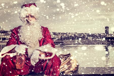 weihnachtsmann lustig: Bad Santa h�lt eine Flasche Weinbrand und Zigarre im Mund Lizenzfreie Bilder