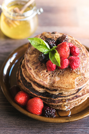 Homemade buckwheat pancakes with berry fruits in the plate,selective focus 版權商用圖片