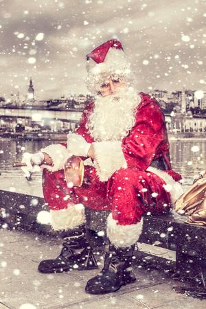 weihnachtsmann lustig: Trauriger Weihnachtsmann mit Zigarre und Flasche Weinbrand im Freien