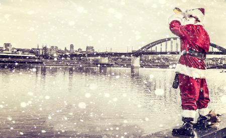 borracho: Papá Noel borracho viendo la ciudad desde la orilla del río