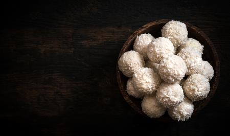 pralines: Sweet coconut pralines in wooden bowl,blank space