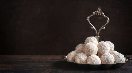 pralines: Coconut pralines served on the wooden background with blank space Stock Photo