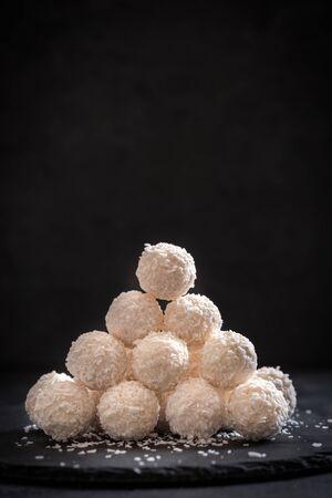 pralines: Sweet coconut pralines on dark background with blank space