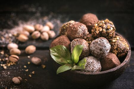 pralines: Variety of sweet homemade chocolate pralines on wooden background,selective focus