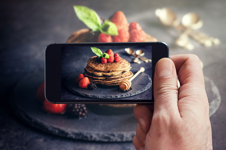 Man photographing wit his phone buckwheat pancakes with fruit Standard-Bild
