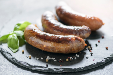 Fried domestic sausages on dark background,selective focus Stock Photo
