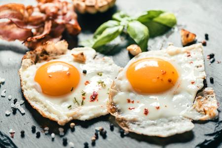 Sluit tot geserveerd gebakken eieren op donkere plaat, selectieve aandacht