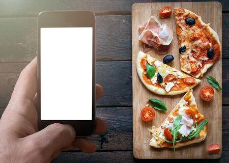 arugola: Slices of mini pizza variety served on wooden board and background,from above and blank space on screen