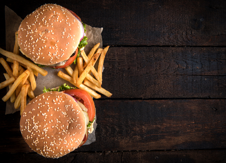 american cuisine: Beef burgers and french fries on wooden background with blank space Stock Photo