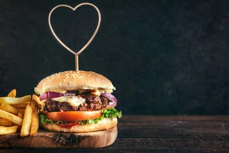Jugosa hamburguesa de carne y patatas fritas en la tabla de madera con espacio en blanco, enfoque selectivo Foto de archivo