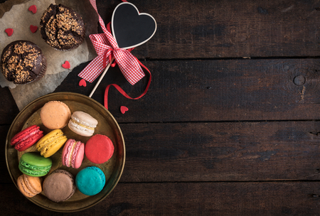 Served chocolate maffins and colorful macaroons cookies on wooden background,valentine day concept and blank space