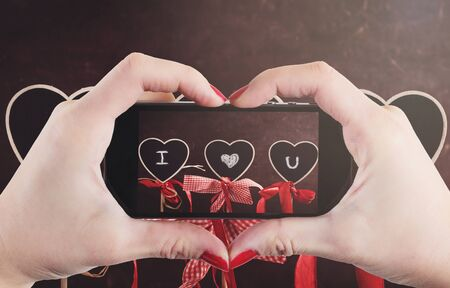 phone message: I love you sign on heart shape chalkboards photographed by woman