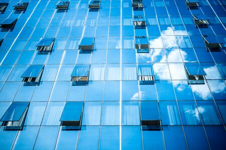 open windows: Building with open windows and clouds reflection