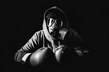 argues: Angry man wearing gas mask and boxing gloves,low key and monochrome Stock Photo