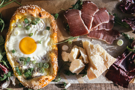 mini pizza: Mini pizza with fried egg, parmesan cheese and ham,selective focus Stock Photo