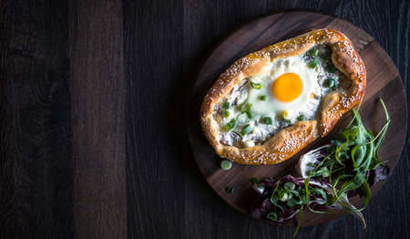 mini pizza: Homemade mini pizza with fried egg and onions served on wooden background with blank space