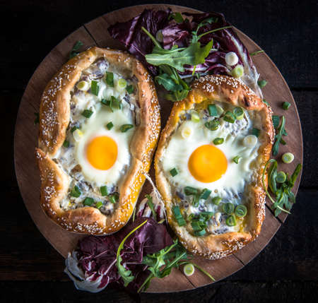 mini pizza: Mini pizza with fried egg on wooden board