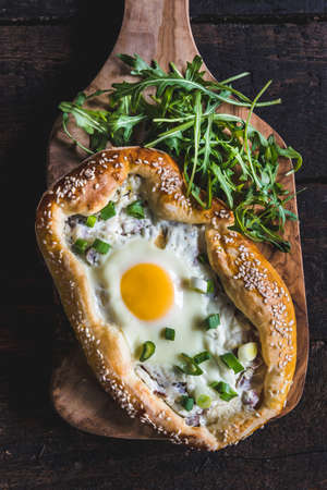mini pizza: Served mini pizza with fried egg on wooden background