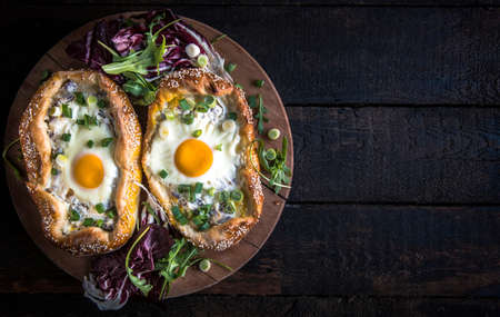 mini pizza: Served mini pizza with fried egg on dark wooden background with blank space