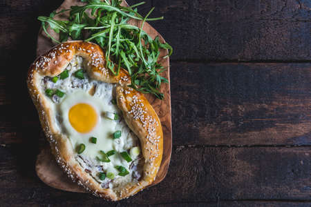 mini pizza: Mini pizza with fried egg on wooden board with blank space Stock Photo