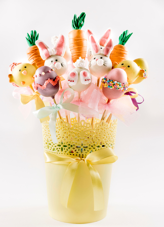 Easter cake pops concept in the basket on white background