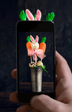 abstract food: Man photographing carrots and bunny cake pops in the metal glass on wooden background Stock Photo