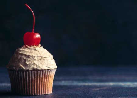 tortas cumpleaÑos: cupcake casera con crema penuts y la cereza en la parte superior, el enfoque selectivo y espacio de la copia