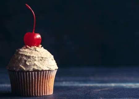 birthday cakes: Homemade cupcake with penuts cream and cherry on the top,selective focus and copy space Stock Photo