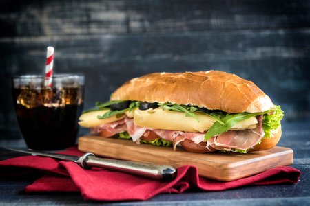Served submarine sandwiches nad coke on the wooden board,selective focus