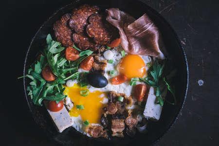 huevos estrellados: Huevos fritos con carne y queso en la sartén
