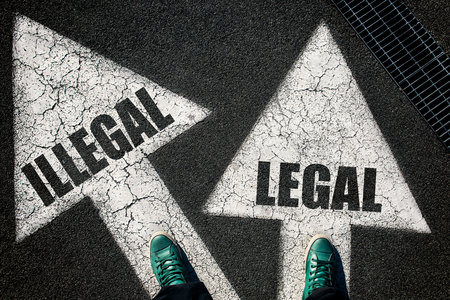Dilemma concept with mans legs on leggal and illegal signs on the road