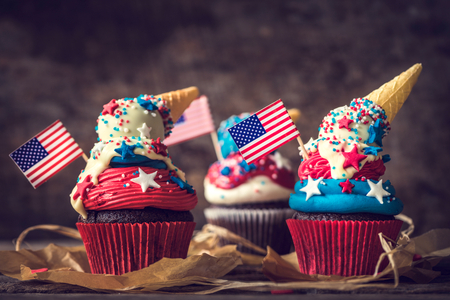 Sweet cup cake with USA flag decoration on top on wooden background,selective focus