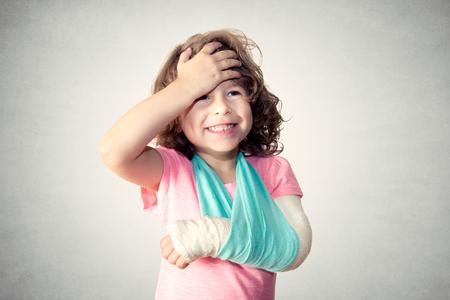niño divertido con fractura en la mano sobre fondo gris