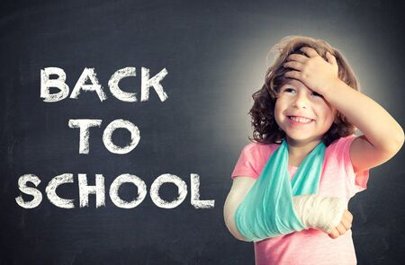 broken back: Child with broken hand holding for her head,back to school concept