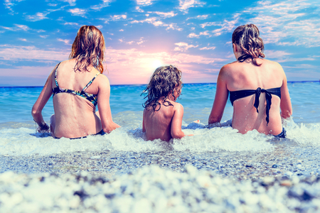 sunligh: Two woman and little girl enjoy on the beach