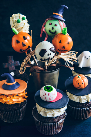 Funny delicious cake pops and cup cakes for Halloween on the table,selective focus