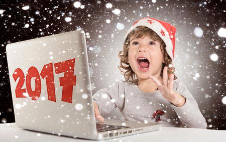 サンタの帽子とラップトップのコンピューターで幸せな小さな子供を祝う新年概念、2017 年