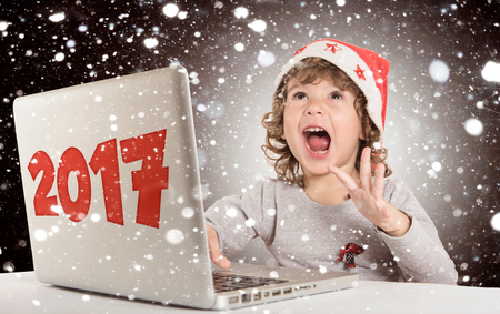 Happy little child with Santa hat and laptop computer celebrate 2017,New Year concept
