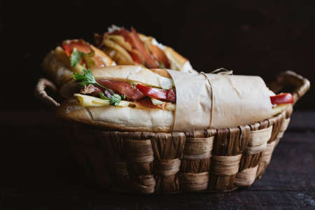 filled roll: Sandwiches served in the wooden  basket Stock Photo